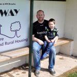 2 football fans sit in AFC Broseley's team dugout