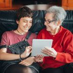 An image on a Granddaughter teaching her grandmother how to use a tablet and develop digital skills.