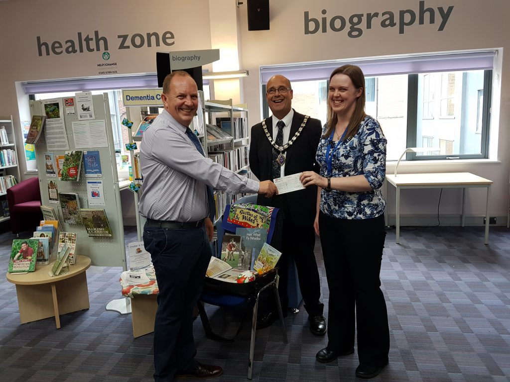 An image of a cheque presentation at Oswestry Library which will help resource further dementia support.