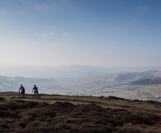 An image of two cyclists on The Portway on the Long Mynd in the Shropshire Hills on a sunny day.