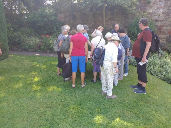 An image of a volunteer and member of University Centre Shrewsbury speaking about the dig finds with interested members of the public at Shrewsbury Castle.