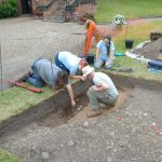 An image of the Shrewsbury Castle dig team discussing layers in part of the trench, trying to understand the relationships between different elements of the archaeology.