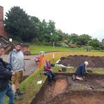 An image of volunteers on the Shrewsbury Castle excavation in and around the trench on a wet Saturday.