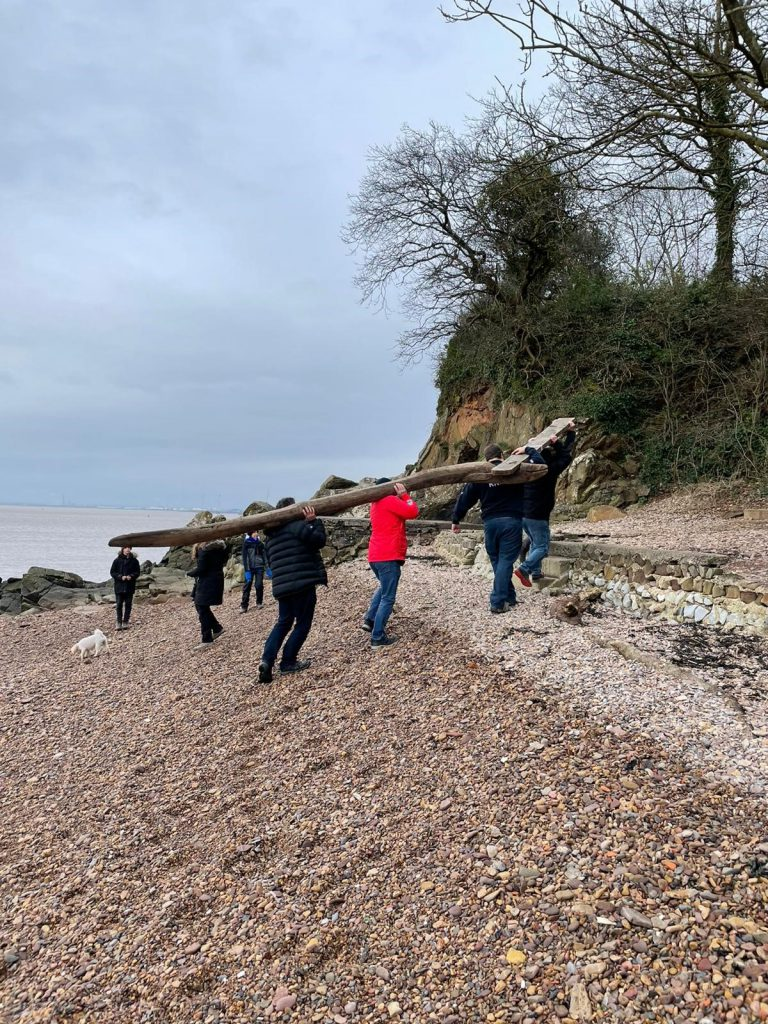 An image of Elvis the wooden Eel being carried from the beach by its finders