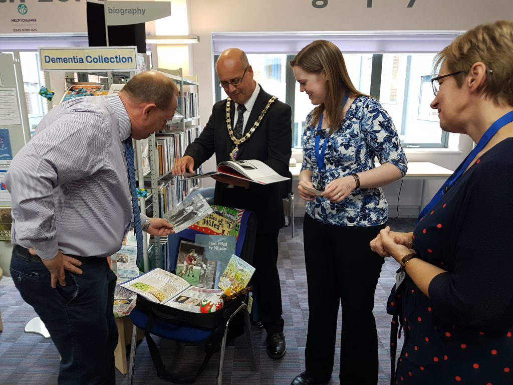 An image of people inspecting the shared memory bags at Oswestry Library that support people living with dementia and their carers.