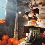 An image of a child wearing a witches hand casting a spell with her wand. She is in a wooden room surrounded by pumpkins. Museums are Magic is happening throughout October half-term 2018 at Shrewsbury Museum and Art Gallery