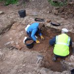 An image of two volunteers working on a previous archaeology project.