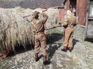 An image of two men in 1940's military dress prodding hay bails with rifles at the Wartime Farm event at Acton Scott Historic Working Farm.