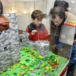 An image of a father and his son looking at the Lego model of Rochester Castle with intrigue in the Brick History exhibition that was at Shrewsbury Museum and Art Gallery from 12 February to 15 April 2018.