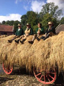 An image of four people in 1940's period dress sat on a hay cart at Acton Scott Historic Working Farm during the Wartime Farm event.