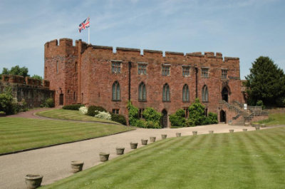 An image of Shrewsbury Castle with the union jack flying at the left. There a lawns and plants that are in pristine condition on a beautiful summer day.