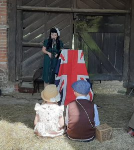 An image of a lady in 1940's period dress singing in front of a union jack flag to children at the Wartime Farm event at Acton Scott Historic Working Farm.