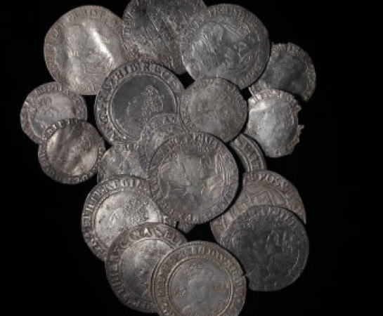 An image of the South Ludlow Hoard. The hoard consists of silver coins on a black background. The South Ludlow Hoard is now on display at Ludlow Museum at The Buttercross. The Hoards is owned by Shropshire Museums who are a service within Shropshire Council.