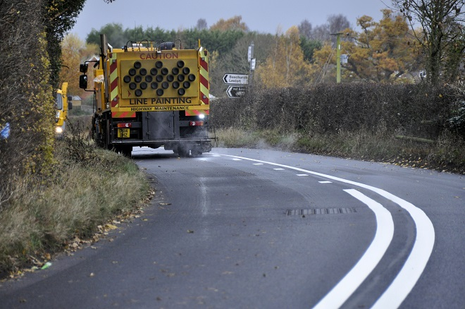 A line painting vehicle on a newly-resurfaced road