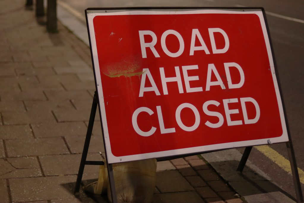 Road ahead closed sign, on pavement