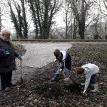 An image of 2 children planting a silver birch tree as part of a community project